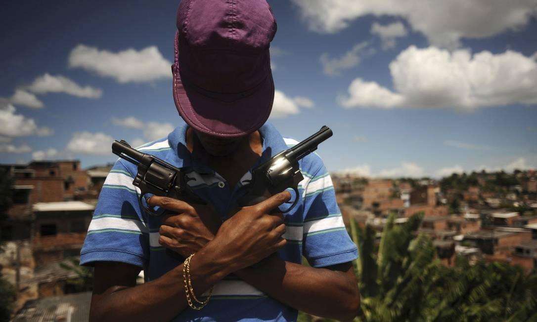 """Numa das favelas de Salvador, o traficante conhecido como """"Veneno"""" mostra parte do arsenal Foto: LUNAE PARRACHO / REUTERS"""