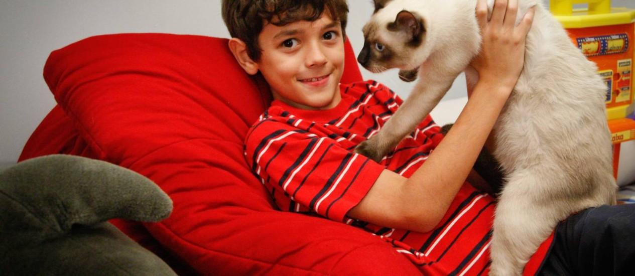 João Pedro, de 9 anos, com dificuldade de se relacionar, ganhou um gatinho há cerca de três meses e agora é ele que tenta conquistar o bichano Foto: Marcos Alves