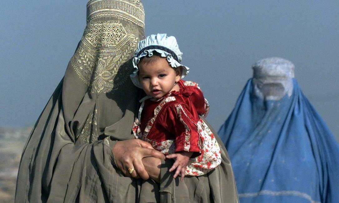 Rigidez. De burca, mãe carrega filha no Afeganistão; maioria dos muçulmanos crê que mulher sempre deve obedecer ao marido Foto: Reuters/8-11-2001