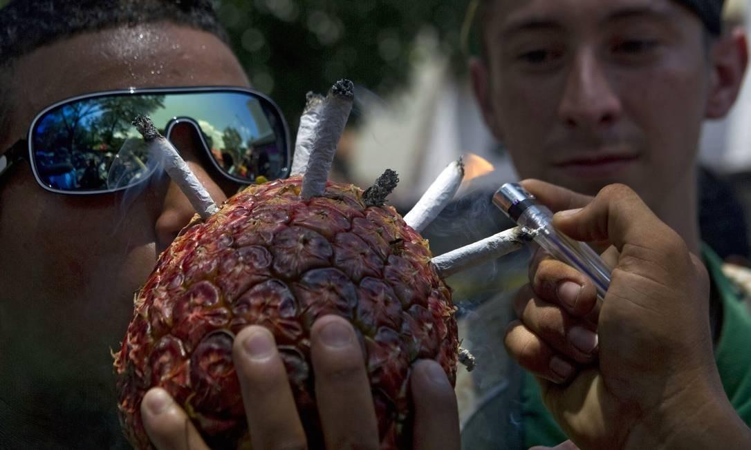 Já este homem escolheu um abacaxi para fumar os cigarros Foto: RAUL ARBOLEDA / AFP