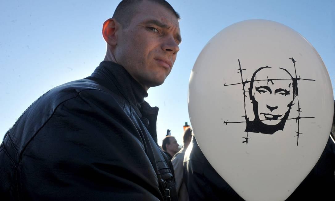 Homem segura balão com uma caricatura de Putin Foto: OLGA MALTSEVA / AFP