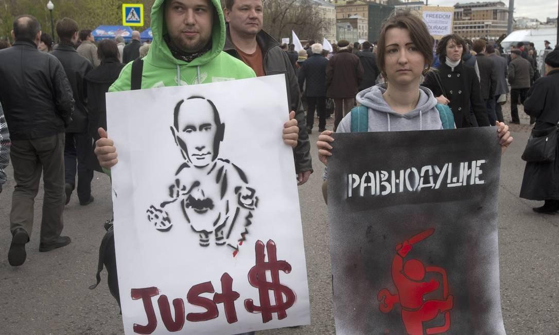 Cartazes fazem denúncias sobre suposto enriquecimento ilícito de Putin Foto: Misha Japaridze / AP