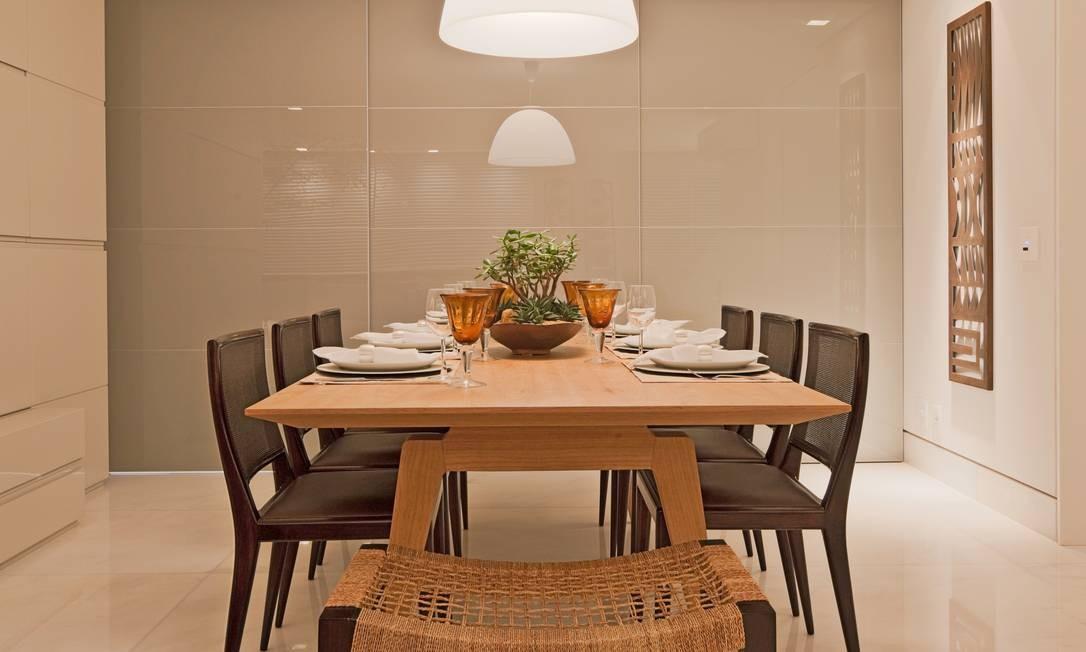 A mesa de jantar em madeira clara contrasta com o piso frio. As cadeiras têm design delicado e encosto em palha, priorizando a leveza Foto: Divulgação