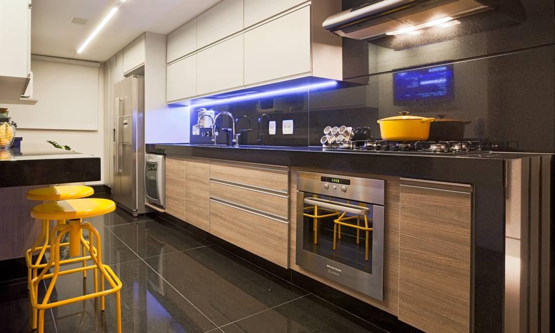 Na cozinha, banquetas amarelas dão o toque moderninho à clássica combinação de preto com madeira Foto: Divulgação
