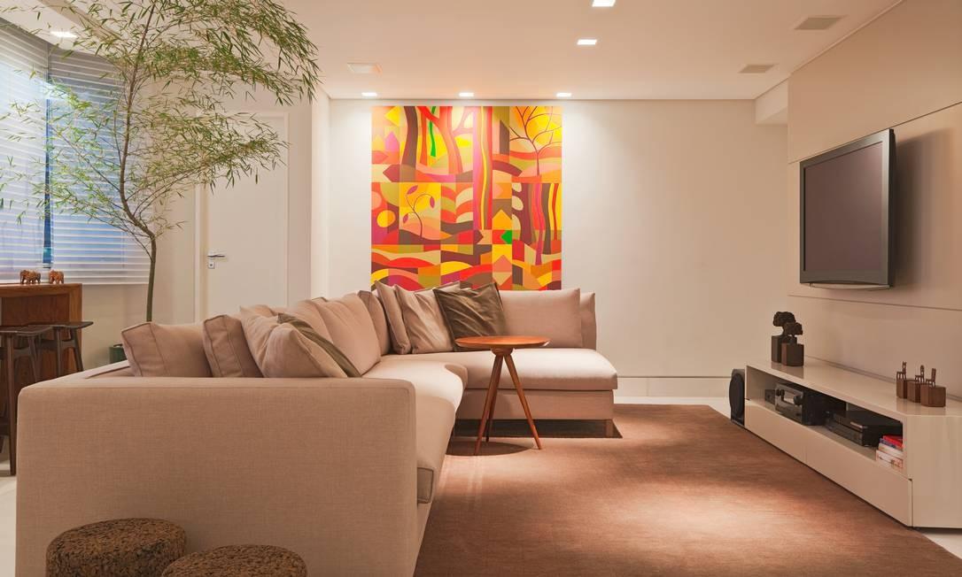 No home theater, o ambiente neutro deixa espaço para se destacar as obras de arte do acervo do cliente, como o painel ao fundo, de J.B. Lazzarini