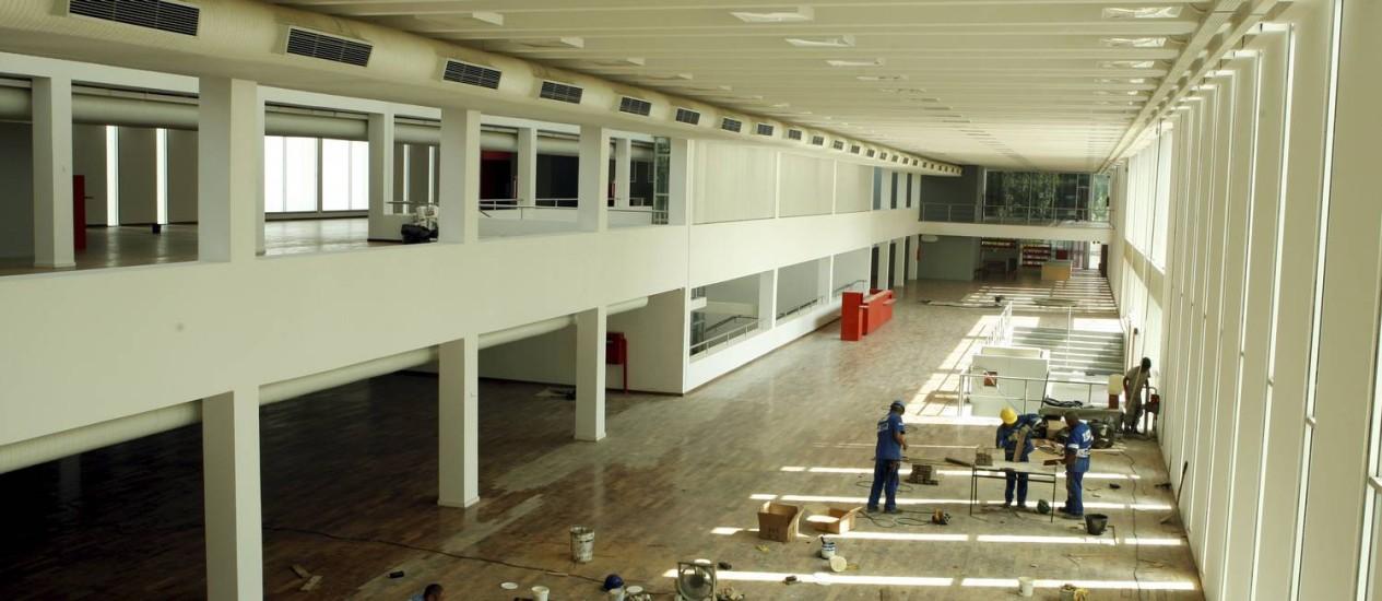 Mãos à obra. Operários instalam o piso do salão do prédio principal: meta é abrir em setembro Foto: Gustavo Stephan / O Globo