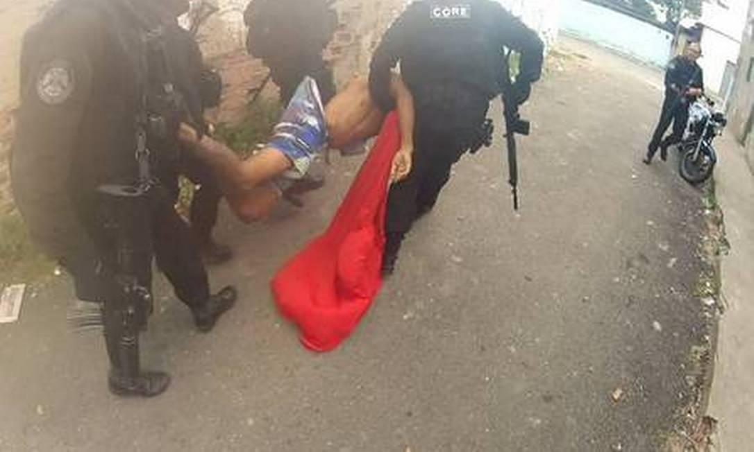 Corpo é carregado por policiais civis para simular auto de resistência Foto: / Reprodução