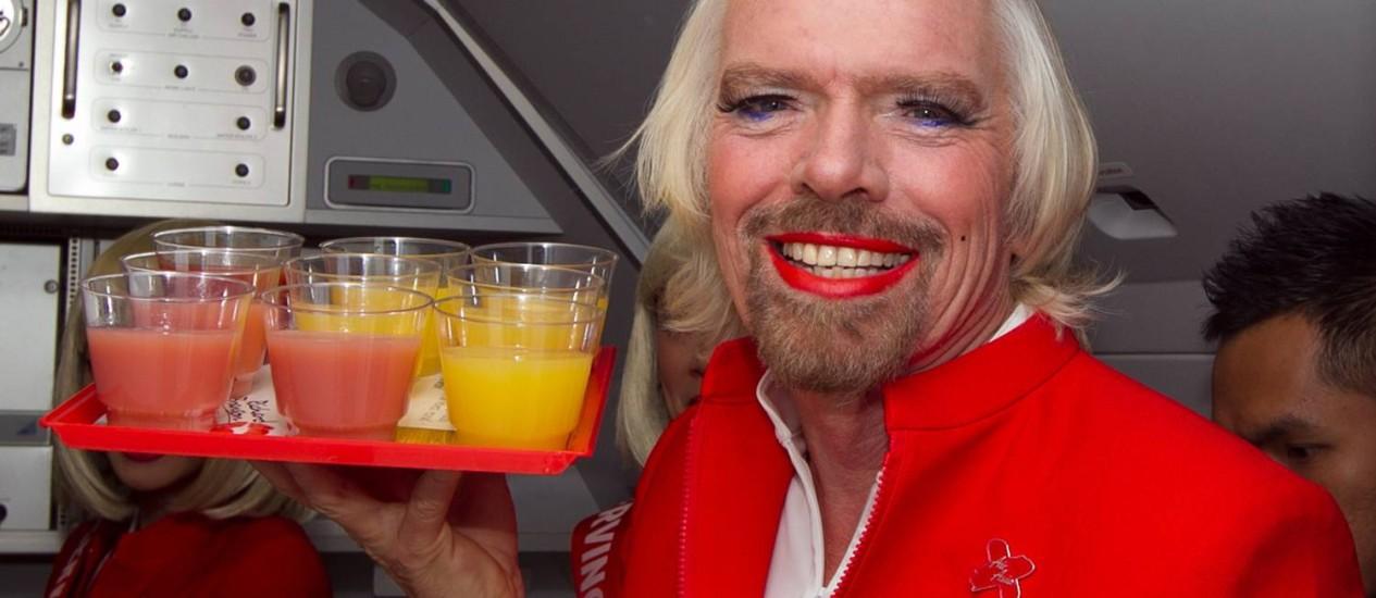 O empresário Richard Branson com uma bandeja de bebidas no voo de Perth, na Austrália, a Kuala Lumour Foto: TONY ASHBY/AFP