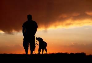 Amizade milenar . Um homem e seu cachorro: novo estudo revela que relação já dura 32 mil anos e funciona tão bem porque evoluiu de forma compartilhada Foto: John Hart / AP