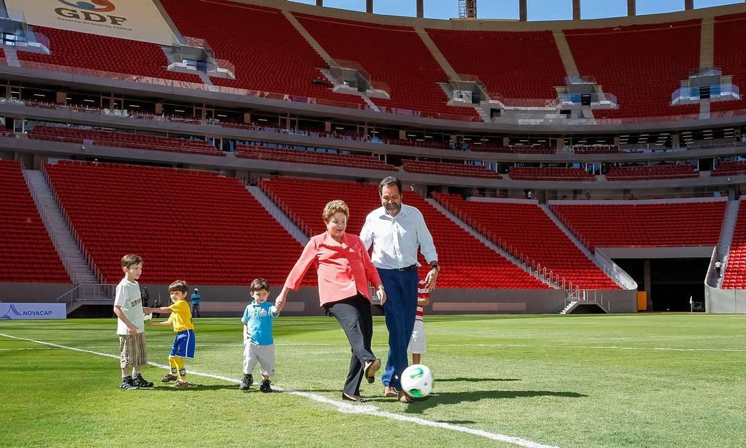 De mão dada com o neto, a presidente Dilma dá o pontapé inicial da inauguração do novo estádio Mané Garrincha, ao lado do governador do Distrito Federal, Agnelo Queiroz, pouco antes da Copa do Mundo Foto: Roberto Stuckert Filho / AFP