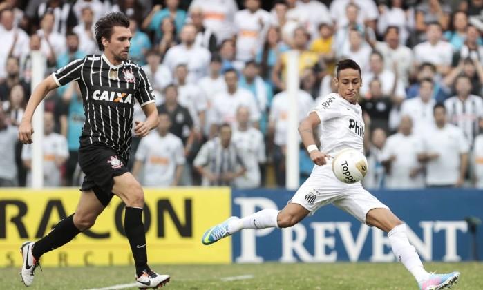 Neymar prepara o chute, e o zagueiro Paulo André, do Corinthians, persegue o atacante do Santos Miguel Schincariol / AFP