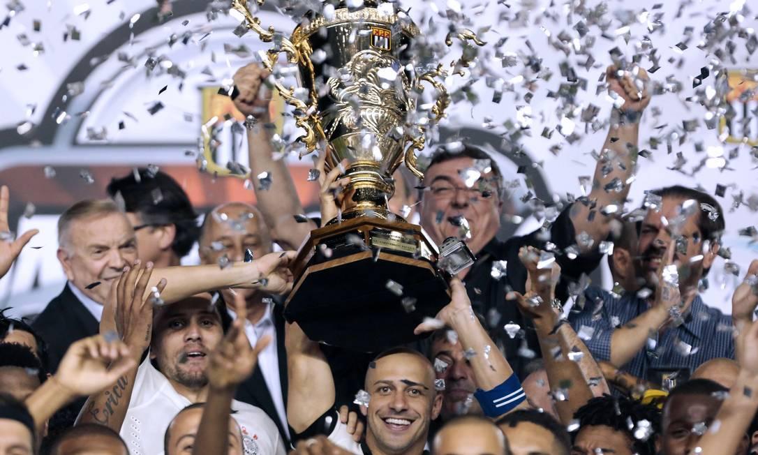 O capitão Alessandro ergue o troféu de campeão paulista de 2013, conquistado pelo Corinthians Miguel Schincariol / AFP