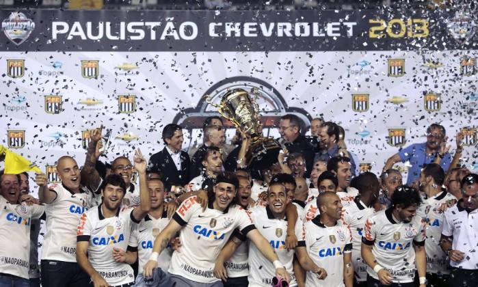 Jogadores do Corinthians festejam no pódio o título paulista de 2013: vitória no primeiro jogo contra o Santos por 2 a 1 e empate no segundo por 1 a 1 Miguel Schincariol / AFP