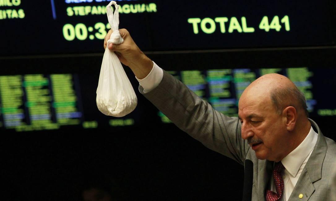 O autor do projeto, deputado federal Osmar Terra (PMDB-RS), durante seu discurso, mostra um saco de plástico e diz que o usuário de crack consome esta quantidade em dez dias Foto: Ailton de Freitas / O Globo