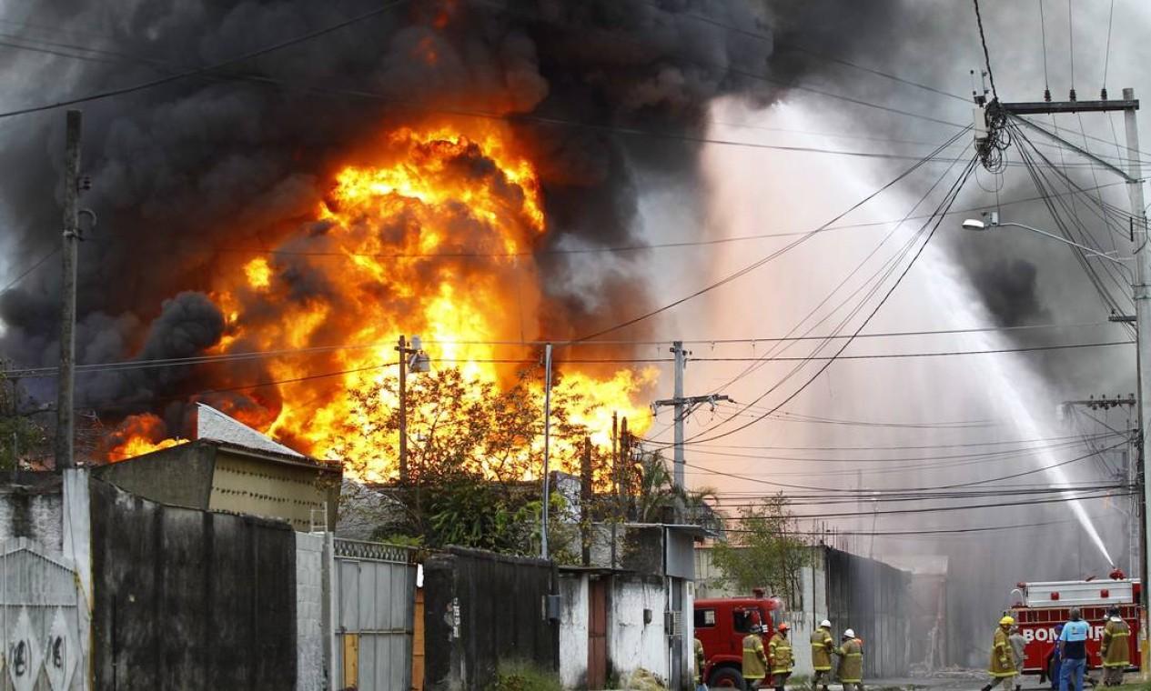 Bombeiros combatem as chamas no depósito que fica em área residencial Foto: Pablo Jacob / Agência O Globo