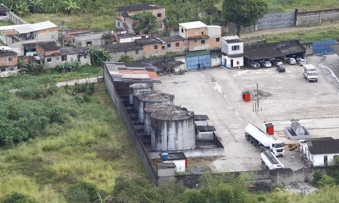 O depósito cercado por muros é um dos que serão fiscalizados pela Secretaria estadual do Ambiente em Duque de Caxias: área abriga residências Foto: Pablo Jacob / O Globo
