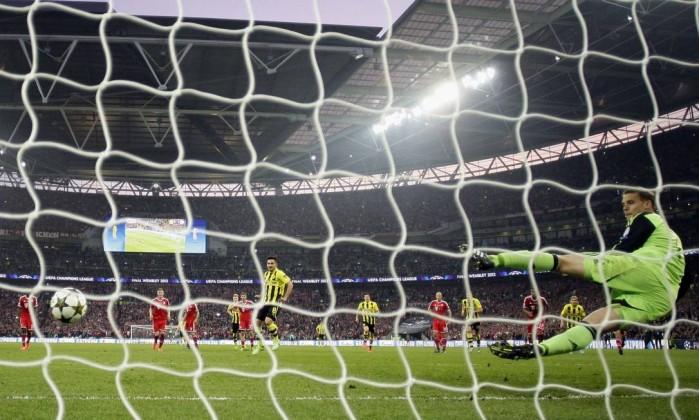 Guendogan (Borussia) chuta a bola no canto oposto do Neuer (Bayern) para deixar tudo igual no placar. Jon Super / AP