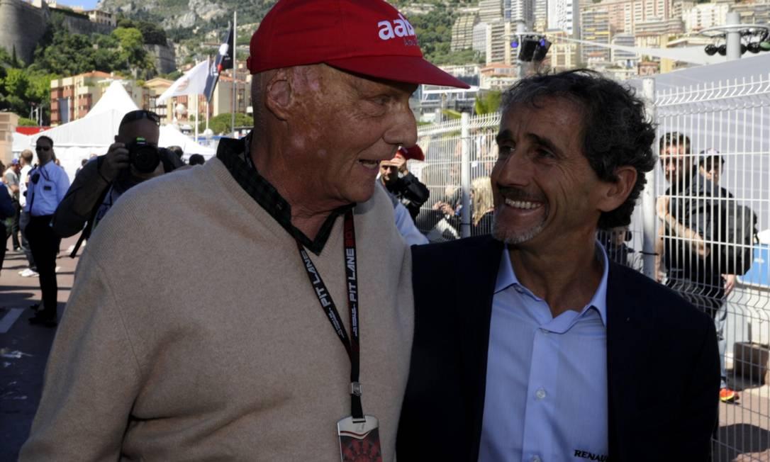 Os ex-pilotos e campeões do mundo Niki Lauda (boné) e Alain Prost se encontram antes da largada. BORIS HORVAT / AFP