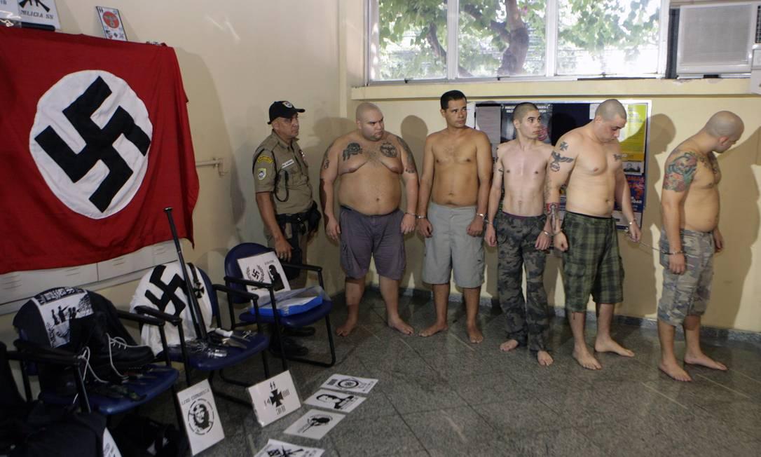 Na 77ª DP (Icaraí), o grupo de acusados faz fila ao lado do material de propaganda nazista apreendido pela polícia: maioria tem tatuagens de suásticas e a cabeça raspada Foto: Luiz Ackermann/27-04-2013 / O Globo