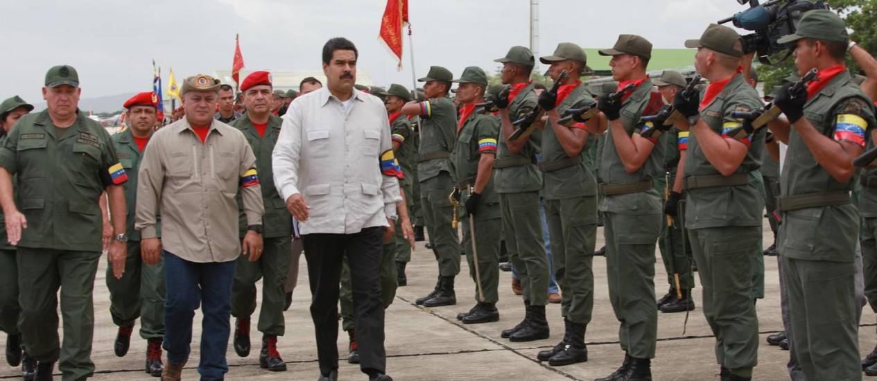 O presidente venezuelano, Nicolás Maduro, o presidente do Congresso, Diosdado Cabello (centro), e o Ministro da Defesa, Diego Molero (esquerda), recebem honras militares durante uma exibição de armas em Maracay, na Venezuela, nesta quinta-feira Foto: PRESIDENCIA / AFP