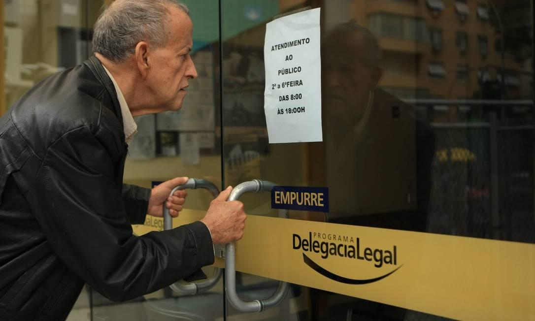 Um homem encontra fechada a Delegacia Especial de Atendimento à Pessoa da Terceira Idade, em Copacabana, Foto: Guilherme Leporace / O Globo