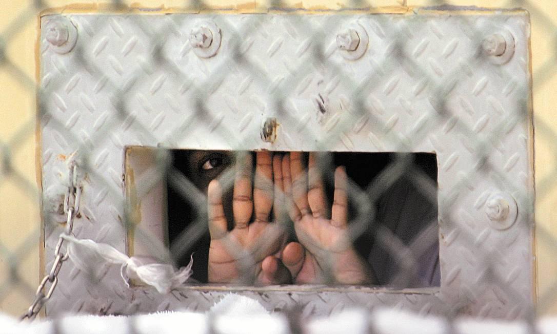 Detento olha através de buraco para entrega de comida na cela: 166 presos continuam sem destino Foto: AP/4-12-2006