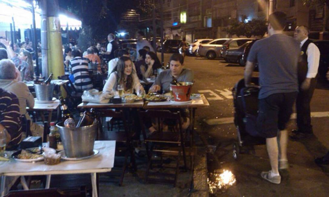 Pai com carrinho de bebê é obrigado a andar pela rua, pois calçada está ocupada por mesas e cadeiras Foto: Eu-Repórter / Leitor Renato Rangel