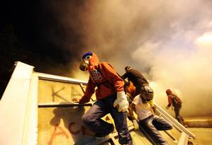 Manifestantes com máscaras antigás se escondem em barricadas durante um dos embates contra a polícia Foto: BULENT KILIC / AFP