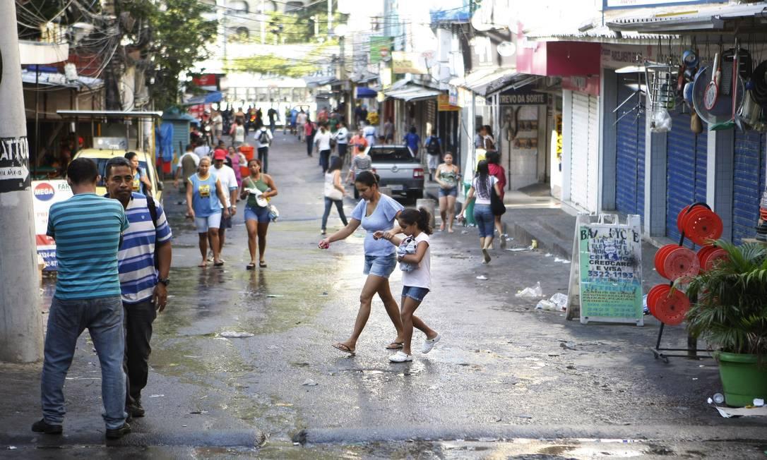 Esgoto. Pedestres caminham sobre a água suja na Via Ápia, uma das principais da comunidade Foto: Eduardo Naddar / Eduardo Naddar
