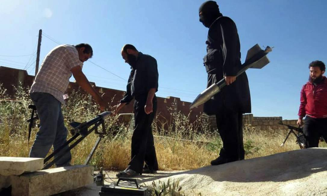 Rebeldes sírios preparam para disparar foguetes fabricados localmente, na província de Idlib, no norte da Síria Foto: AP