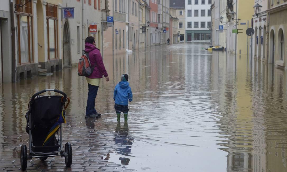 Uma mulher e uma criança caminham por uma rua alagada pelo rio Elbe, em Pirna, na Alemanha Foto: JOHANNES EISELE / AFP