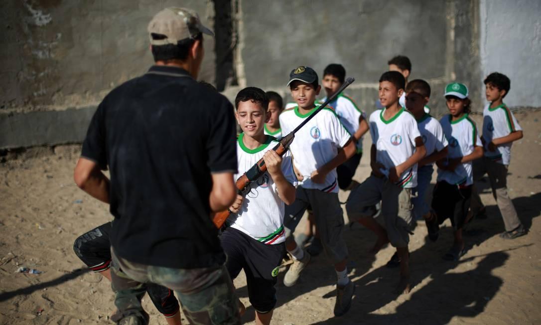 Garotos palestinos passam parte de suas férias de verão treinando em acampamentos do Hamas na Faixa de Gaza. No local, eles aprendem a manusear armas Foto: MOHAMMED ABED / AFP