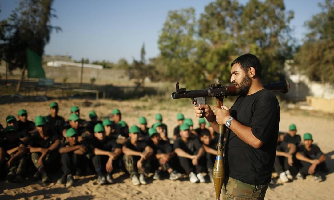 Um militante do Hamas ensina jovens palestinos como usar um lança-granadas Foto: MOHAMMED SALEM / REUTERS