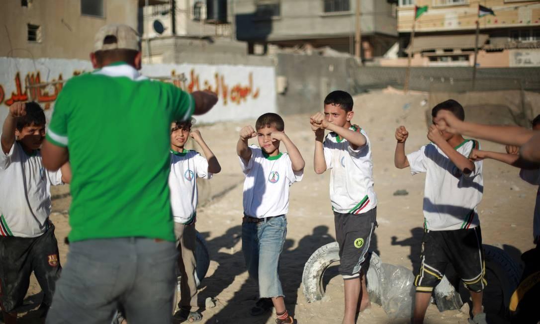 As crianças de Gaza que vão para a colônia de férias ainda aprendem lições sobre o Islã, doutrinação política e, em alguns casos, até treinamento paramilitar Foto: MOHAMMED ABED / AFP