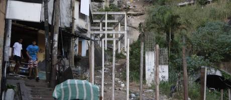 Morador da Rocinha enfrenta a escadaria morro acima passando ao lado da estrutura inacabada do plano inclinado prometida no PAC 1 Foto: Marcos Tristão / O Globo