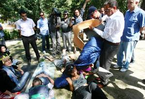 Um policial retira os pertences de manifestantes turcos sentados no Parque Kugulu, em Ancara Foto: ADEM ALTAN / AFP
