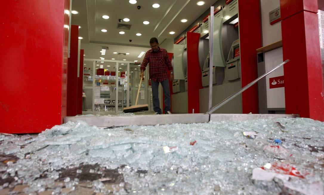 Homem limpa uma das agências bancarias que tiveram o vidro quebrado por manifestantes na Avenida Presidente Vargas Foto: Marcos Tristão / Agência O Globo