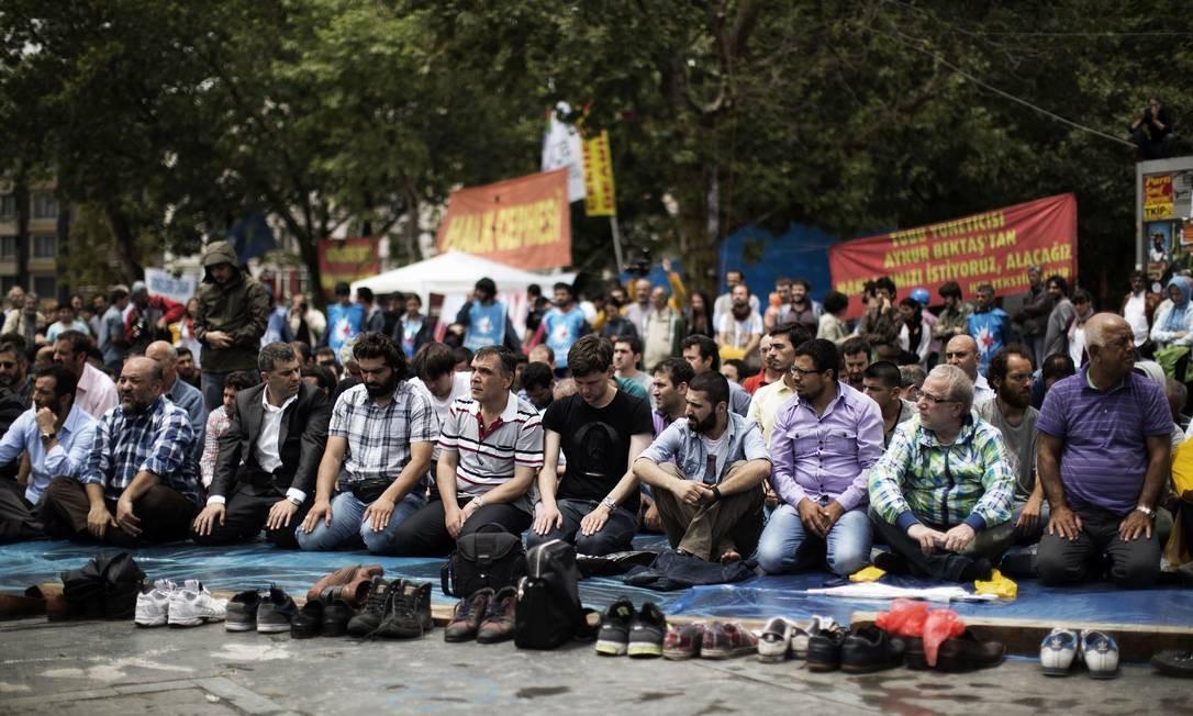 Manifestantes turcos muçulmanos oram na entrada do Parque Gezi, em Istambul Foto: MARCO LONGARI / AFP