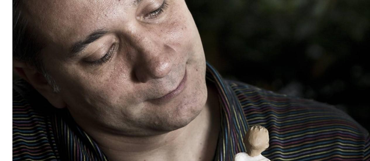 Bruno segura um boneco que representa o filho, que fica sala de casa Foto: Mônica Imbuzeiro / O Globo