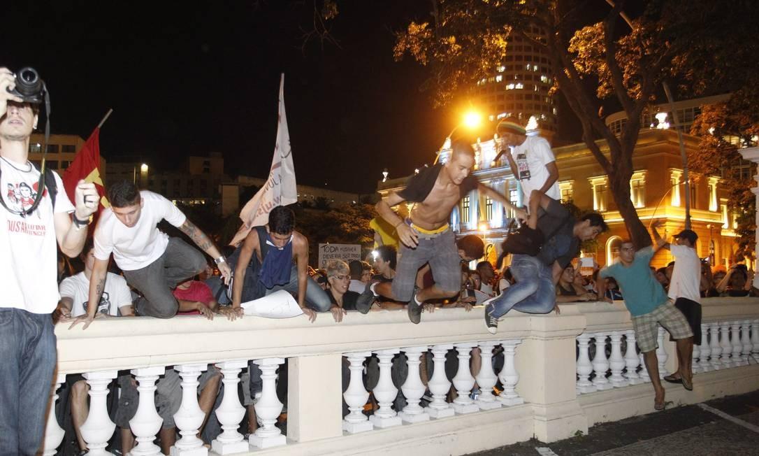 Manifestantes pulam o muro da Câmara Municipal Foto: Marcelo Carnaval / Agência O Globo