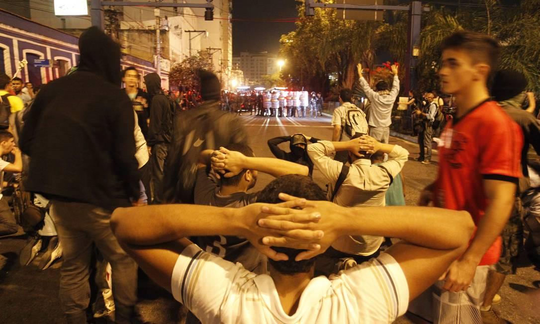 Manifestantes com as mãos na cabeça diante dos policiais Foto: Marcelo Carnaval / O Globo