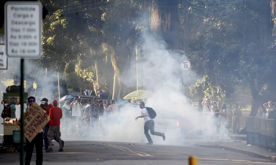 Manifestante corre após a explosão de uma bomba de gás lacrimogêneo Foto: Pedro Kirilos / Agência O Globo