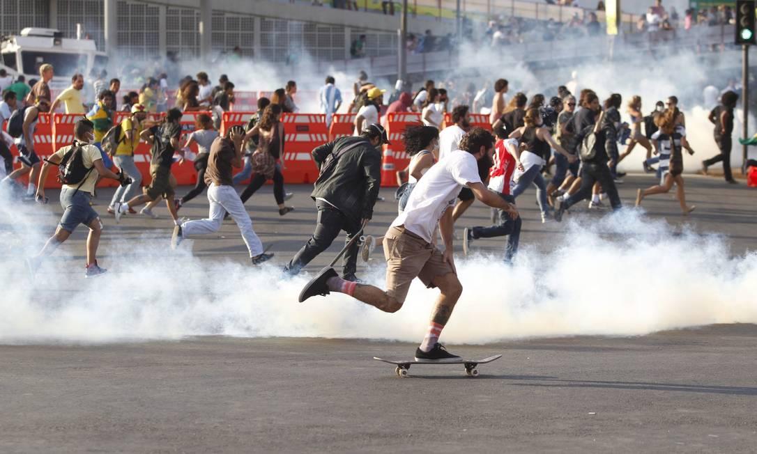 Manifestante foge em cima de um skate de uma bomba de gás lacrimogêneo atirada pela Tropa de Choque da Polícia Militar Foto: Pedro Kirilos / Agência O Globo