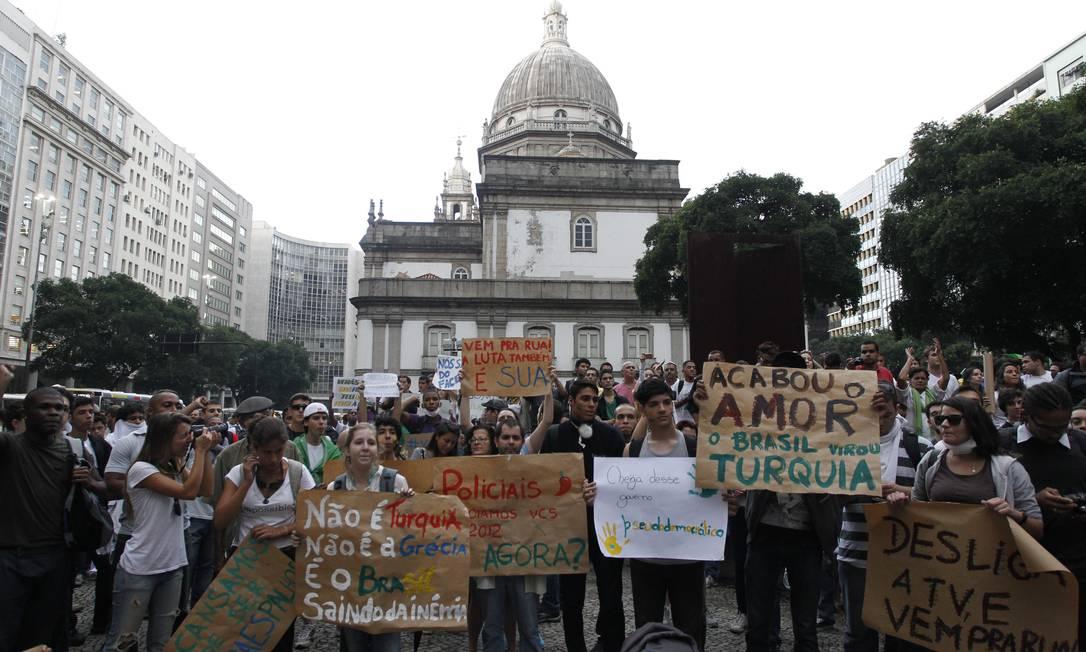 Manifestantes exibem cartazes durante concentração na Candelária Domingos Peixoto / Agência O Globo