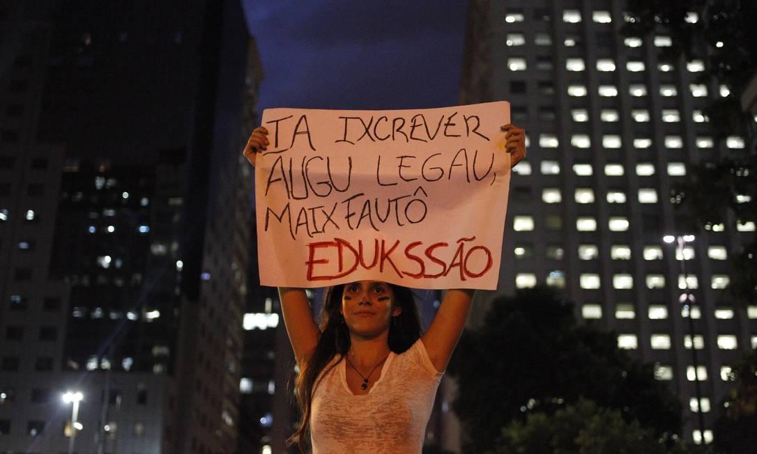 Manifestante, com pitura nas cores da bandeira do Brasil no rosto, segura cartaz que critica o investimento em educação durante o protesto no Centro Pedro Kirilos / Agência O Globo