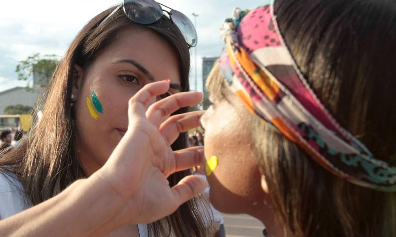 Jovens pintam o rosto com as cores da bandeira brasileira em Brasília Foto: Givaldo Barbosa / Agência O Globo