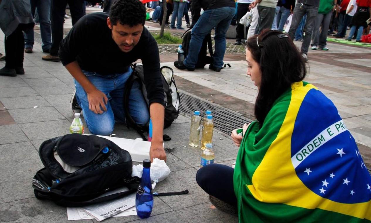 Uma manifestante coberta pela bandeira brasileira se prepara para participar do protesto em São Paulo Foto: Ale Vianna / Brazil Photo Press