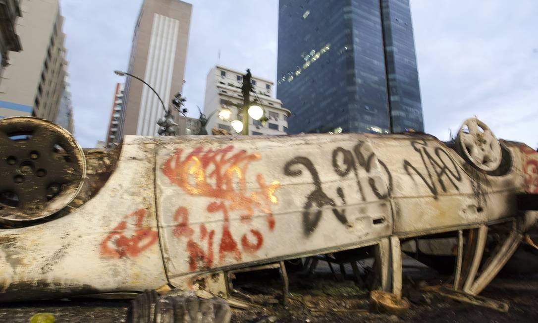 O carro de Fabrício foi virado e incendiado por um grupo no Centro do Rio Foto: Fernando Quevedo / O Globo