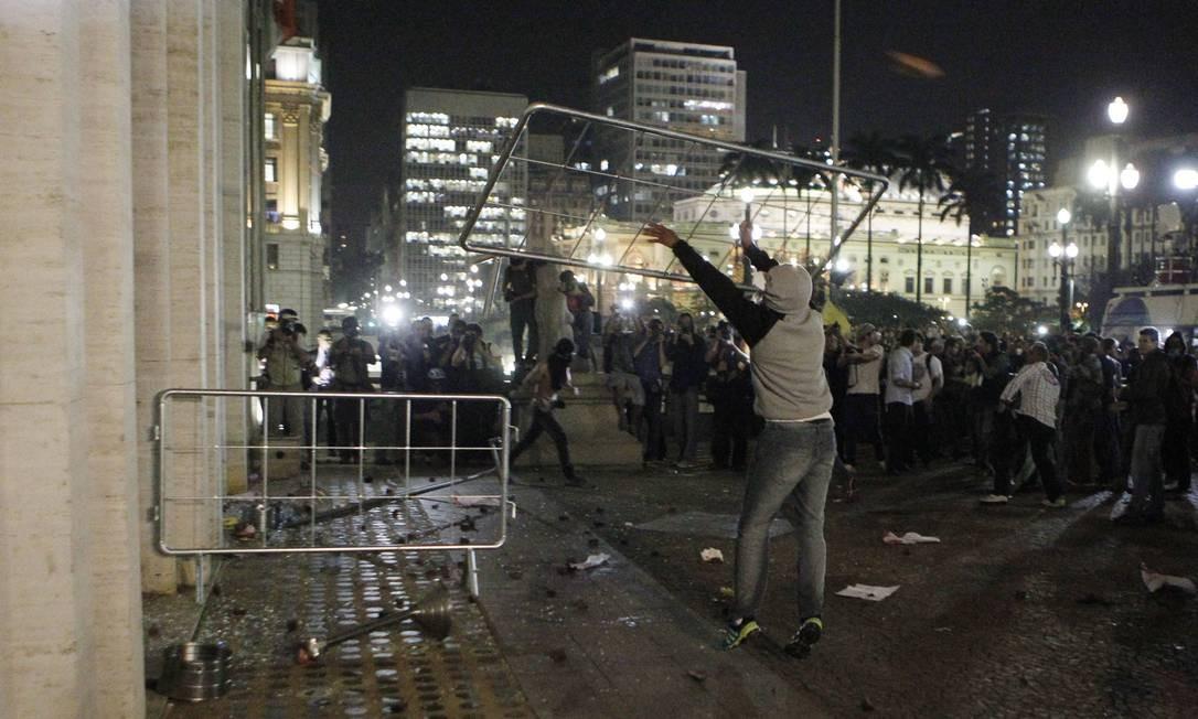 Um dos participantes do protesto joga a grade de proteção contra o prédio da prefeitura de São Paulo Michel Filho / Agência O Globo