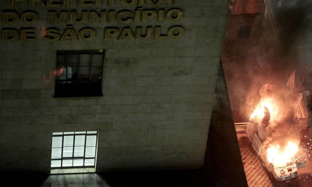 Um veículo de reportagem da TV Record é incendiado durante o protesto em frente à prefeitura de São Paulo Miguel Schincariol / AFP